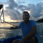 Picture of Bastian Sarh sitting on sailboat at sunset.